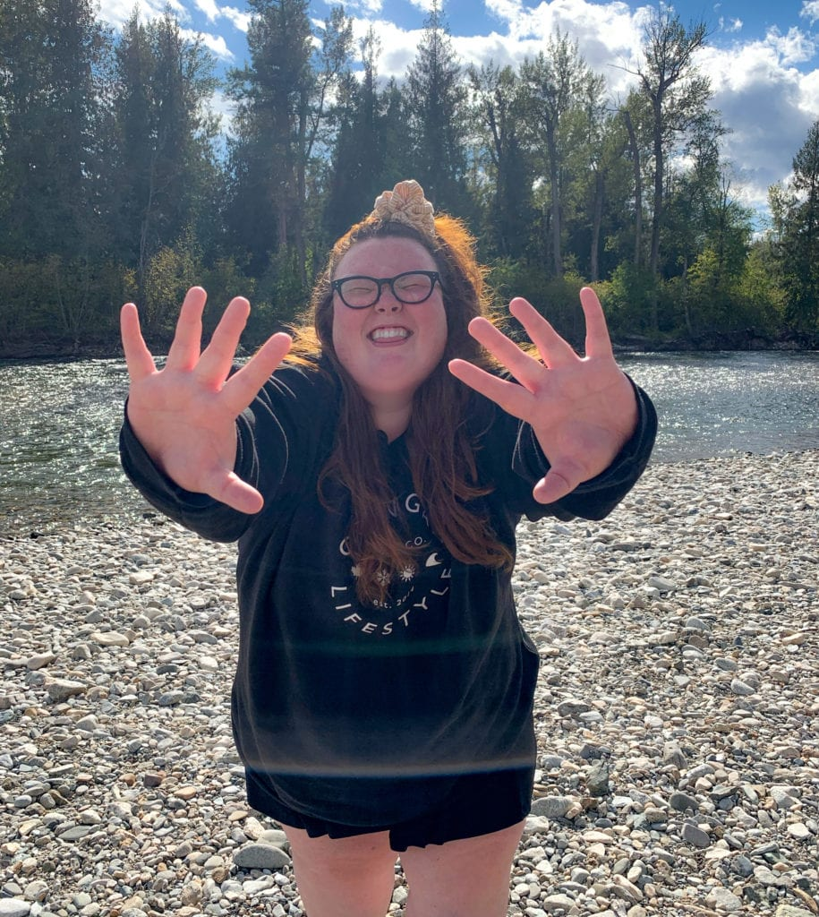 Beth Quirie on a creek bed with her hands up.